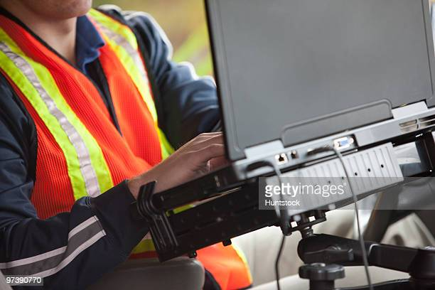 Inspector using a laptop in a vehicle
