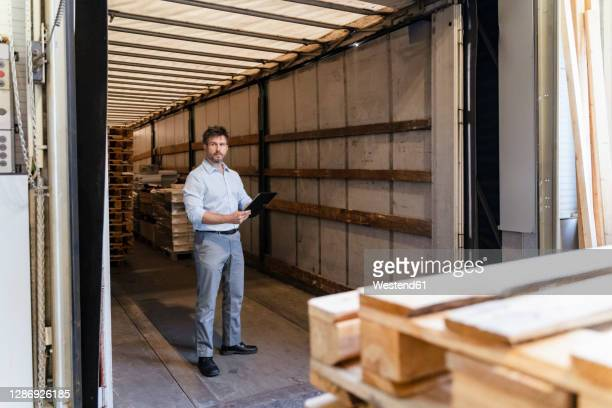 inspector with digital tablet loading material while standing in delivery truck - beladen stock-fotos und bilder