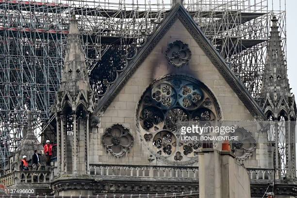 TOPSHOT Inspectors are seen on the roof of the landmark NotreDame Cathedral in central Paris on April 16 the day after a fire ripped through its main...