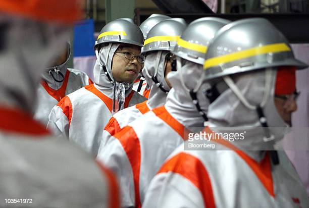 Inspectors look at a rod containing plutoniumuranium mixed oxide known as MOX fuel being loaded to the No 3 reactor at Tokyo Electric Power Co's...