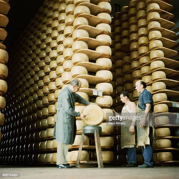 Inspectors look over a cheese wheel in a warehouse which is the largest storage facility for Parmesan cheese in Parma Italy