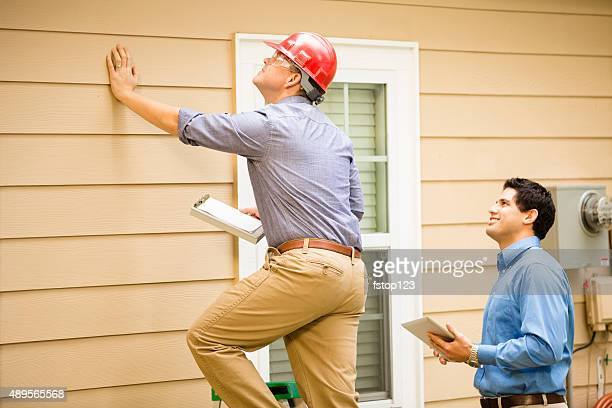 inspectors or blue collar workers examine building wall, foundation. outdoors. - inspector stock pictures, royalty-free photos & images