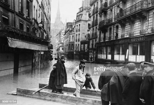 Installation de parpaings flottants pour la circulation des Parisiens dans les rues inondées par la crue de la Seine en 1910 à Paris France