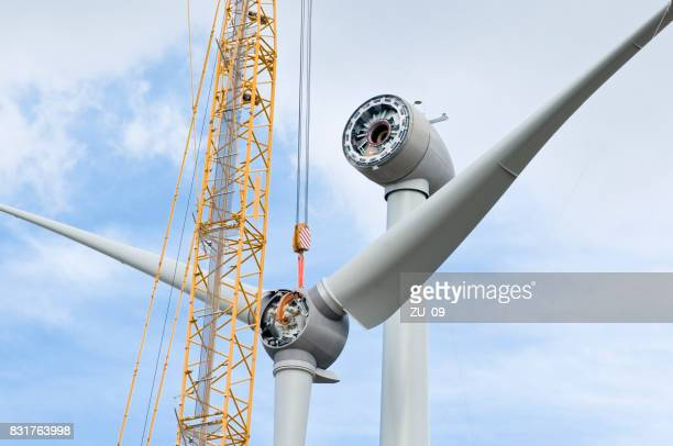 installation the rotor blades on a wind turbine - erection stock photos and pictures