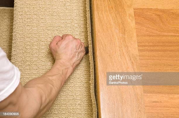 Installer Cutting Carpet Stair Tread Near Hardwood Landing