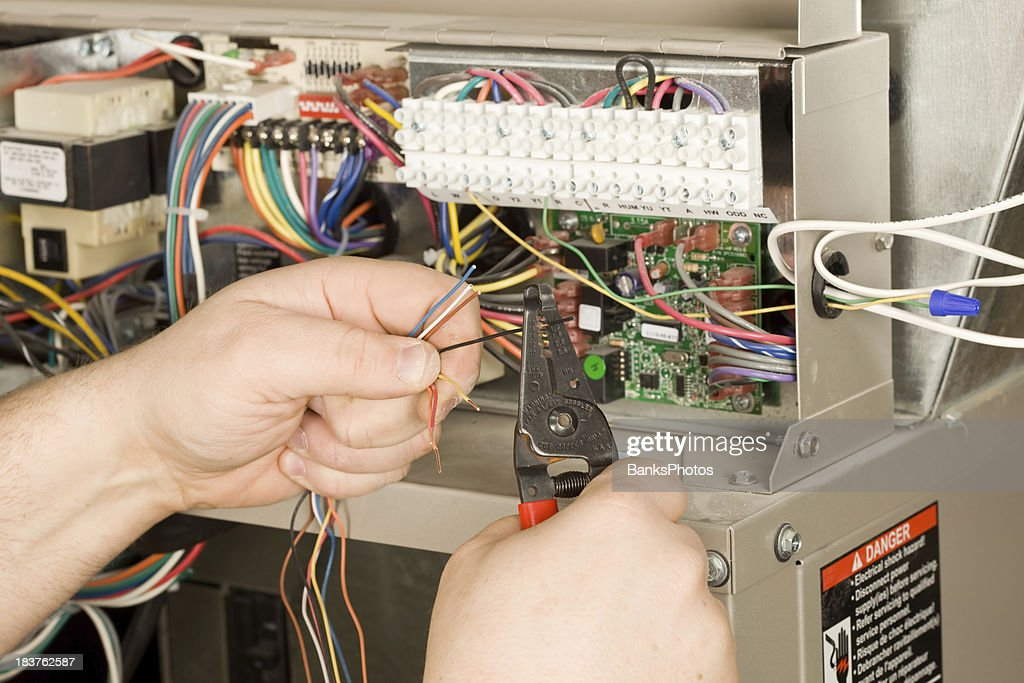 HVAC Installer Strips Small Wires for a new Residential Furnace : Stock Photo