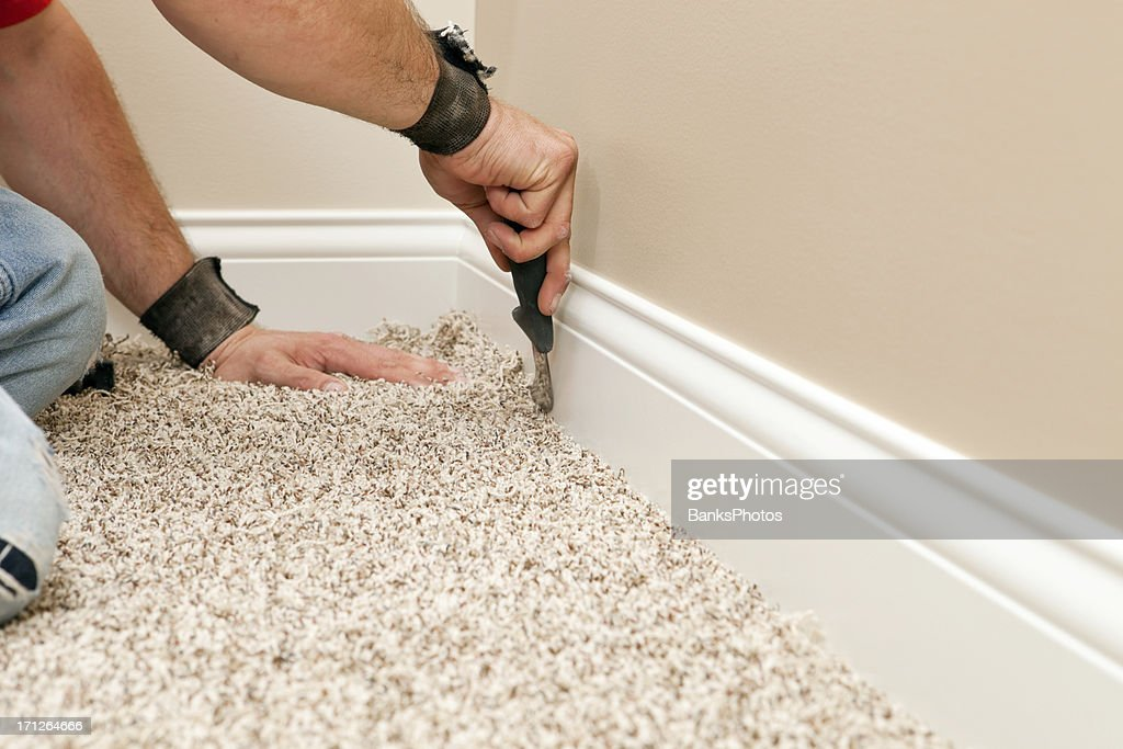 Installer Using Carpet Knife to Tuck New Floor : Stock Photo