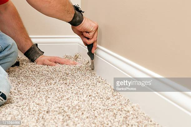 installer using carpet knife to tuck new floor - tapijt stockfoto's en -beelden