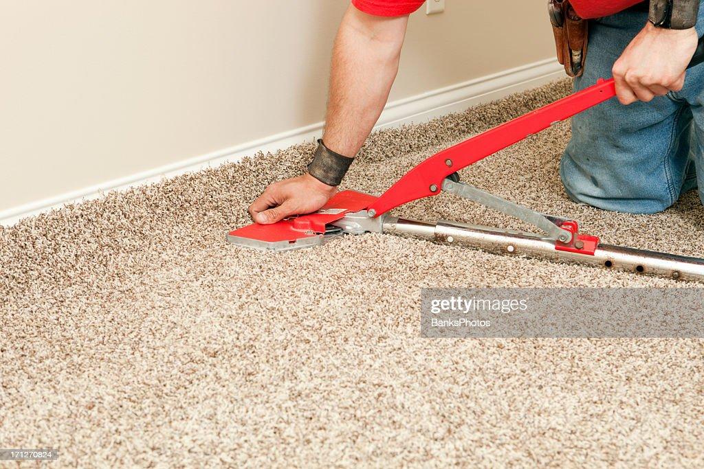 Installer Using Carpet Stretcher on New Bedroom Floor : Stock Photo