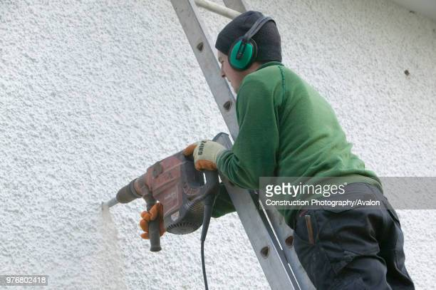 Installing cavity wall insulation into a house to increase its energy efficiency and reduce the carbon emmissions from central heating Ambleside...