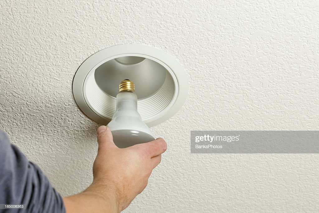 Installing incandescent recessed light bulb in ceiling fixture installing incandescent recessed light bulb in ceiling fixture stock photo aloadofball Images