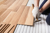 Installing laminated floor, detail on man hands fixing one tile with hammer, over white foam base layer