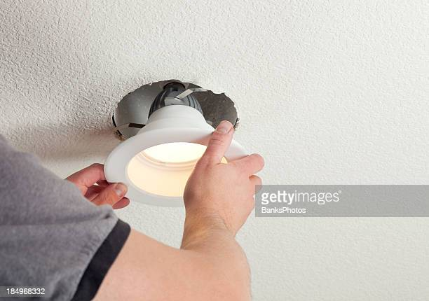 installing led retrofit bulb into ceiling fixture - illuminated stock pictures, royalty-free photos & images