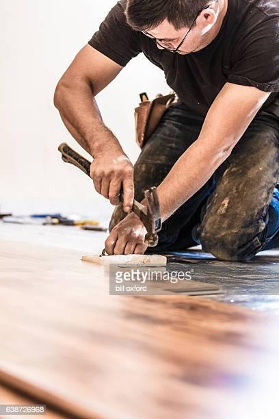 installing wood flooring - hammering - installieren stock-fotos und bilder