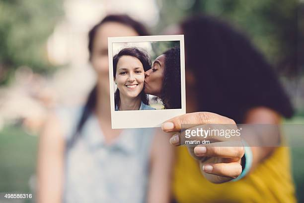 Instant photo of girl kissing friend on the cheek