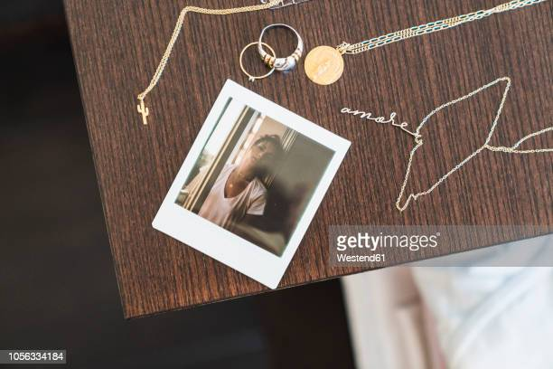instant photo of young woman next to jewelry on wooden table - collar fotografías e imágenes de stock