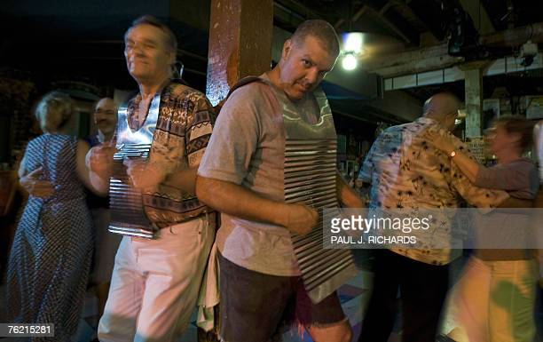 Instead of dancing, music fans Jimmy and his son John Burn play their personal Washboard, often called a Frottoir or Rubboard as others dance to the...