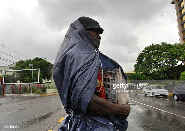 Instead of hunkering down hard working Voltiman Hebert puts up with a heavy rain brought on by incoming Hurricane Dean as he sells newspapers in...