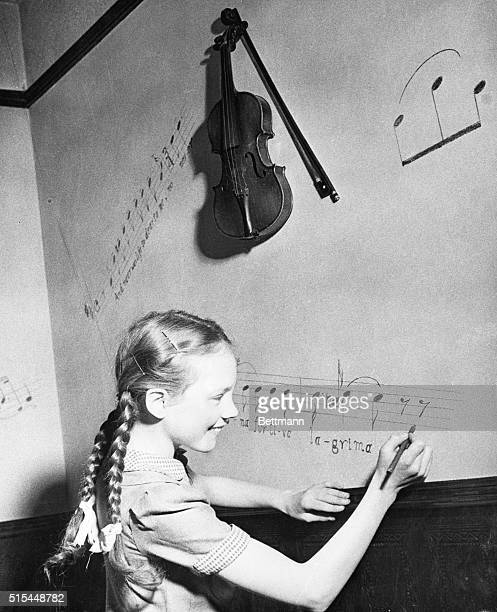 Instead of the usual playroom, Julie has a music room in the Andrews home. Everything in the room pertains to music. Julie is decorating a wall with...
