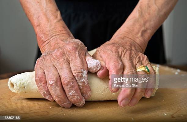 Instead of using a mixer Hok Kun Ng of Overland Park uses his hands to pound and shape flour and water into the dough for his pork and cabbage...