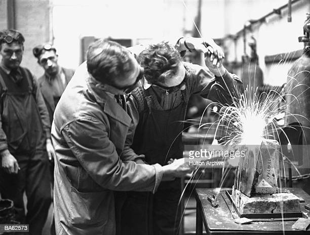 Instructor assisting pupil in welding class (B&W)