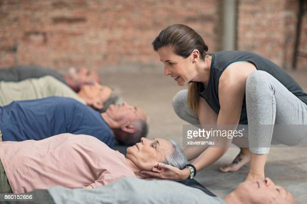 Instructor assisting senior man in yoga exercising