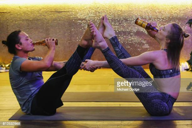 Instructor Emma Joubert performs a Beer Yoga stretch with a participant at a Beer Yoga class at The Emerson on July 11 2017 in Melbourne Australia...
