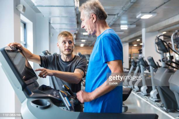 instructor explaining treadmill functions to senior man - drug rehab stock pictures, royalty-free photos & images