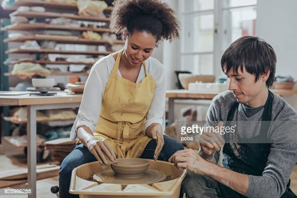 instructor guiding pottery student  in art studio - pottery stock pictures, royalty-free photos & images