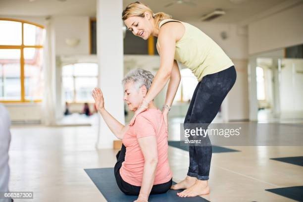 instructor helping senior woman in doing yoga - yoga teacher stock pictures, royalty-free photos & images