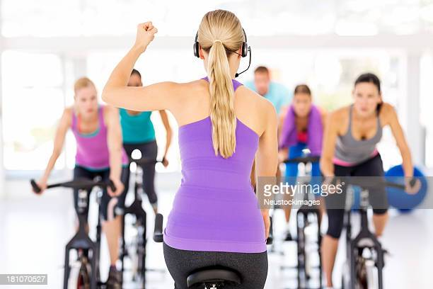Instructor Inspiring Spinning Class In Gym