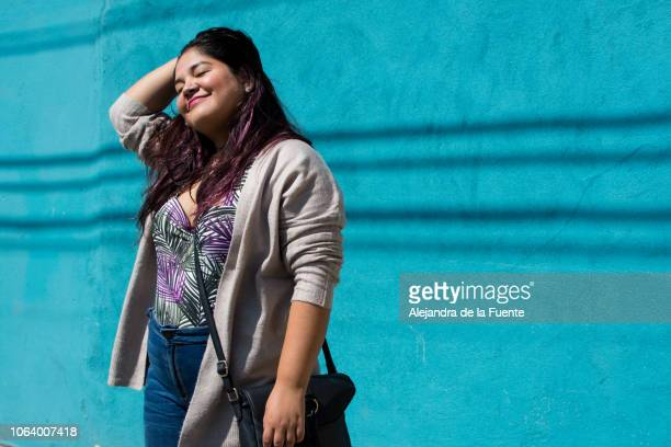 portrait of a beautiful latina woman standing in front of a blue wall. - chubby - fotografias e filmes do acervo