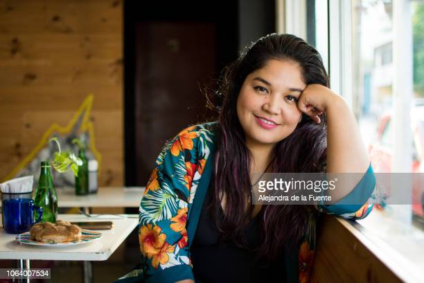 portrait of a young latina woman sitting at a restaurant - chubby woman stock-fotos und bilder