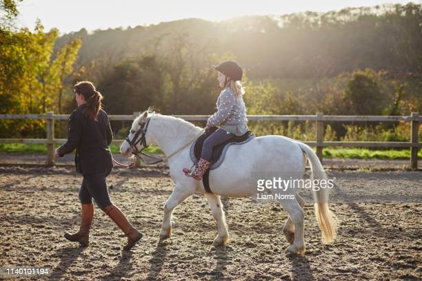 instructor leading girl riding white pony in equestrian arena - pony stock pictures, royalty-free photos & images