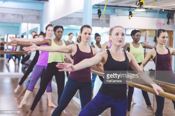 instructor leads a multiethnic group of women through a barre workout - human arm stock pictures, royalty-free photos & images