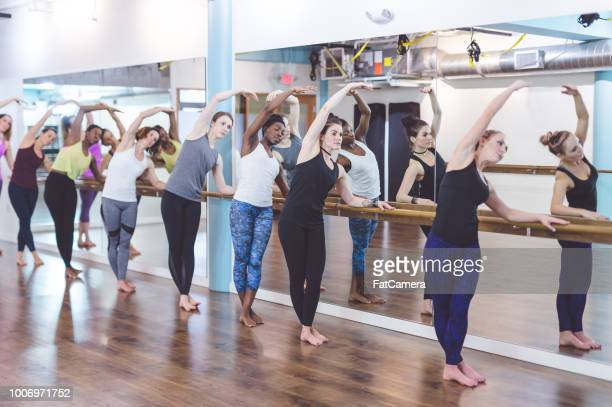 Instructor leads a multiethnic group of women through a barre workout