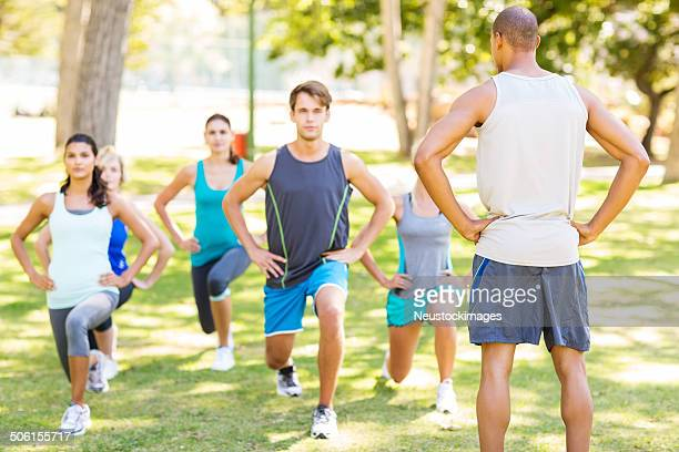 instructor looking at people doing lunges in park - barracks stock pictures, royalty-free photos & images