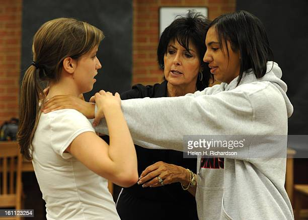 Instructor Margaret Chavez shows students Alexis Scobie left and Hannah Pinto right how to break out of a choke hold Anne Diamond who is a mother of...