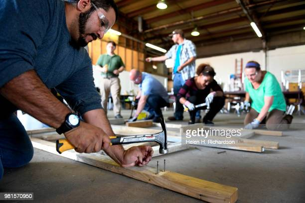 Instructor Moses Alvarez left teaches the finer points of building concrete forms to students taking part in the Construction Careers Now program at...