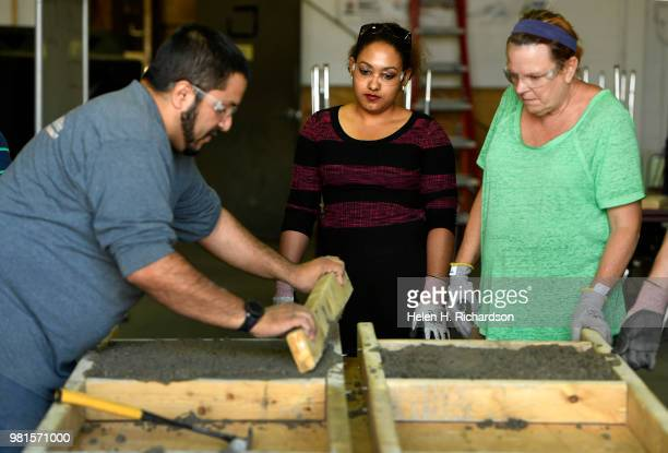 Instructor Moses Alvarez left teaches the finer points of concrete finishing to students Rafelina Garibay middle and Darlene Wilkins right as they...