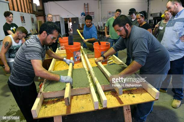 Instructor Moses Alvarez right teaches the finer points of concrete finishing to Muhammad Sarwari left and other students taking part in the...