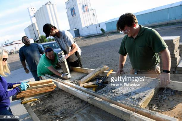 Instructor Moses Alvarez second from left in back teaches students how to take dried concrete out of hand built forms during the Construction Careers...