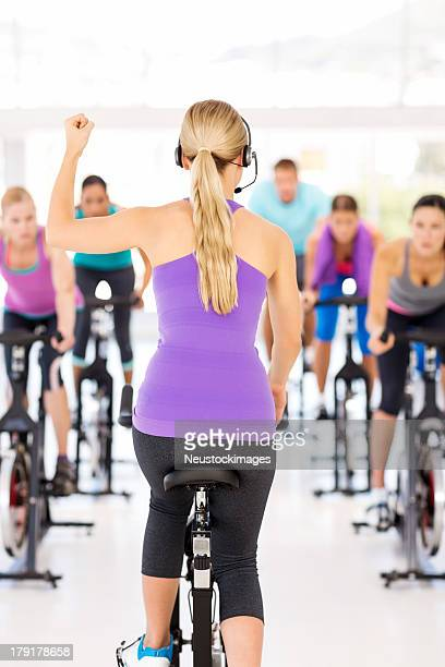 Instructor Motivating Class While Cycling On Bikes In Gym