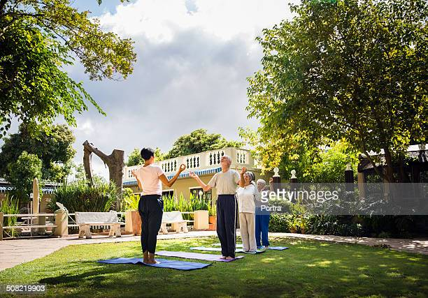 Instructor performing yoga with senior people