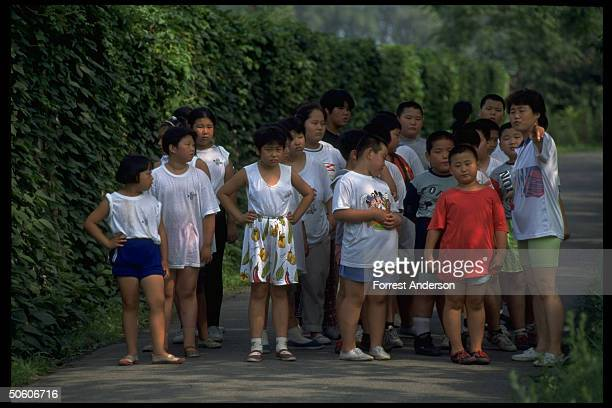 Instructor pointing out sight to boys girls out for jog at weight loss camp for obese children aged 816 paying 780 yuan fee for 10day stay