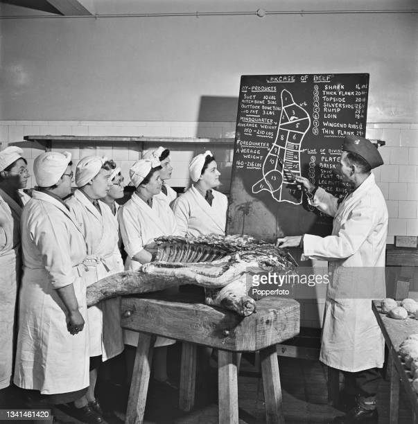 Instructor Sergeant Watchus teaches the anatomy of the meat ration to a group of students with the aid of a blackboard and a carcass of beef in a...
