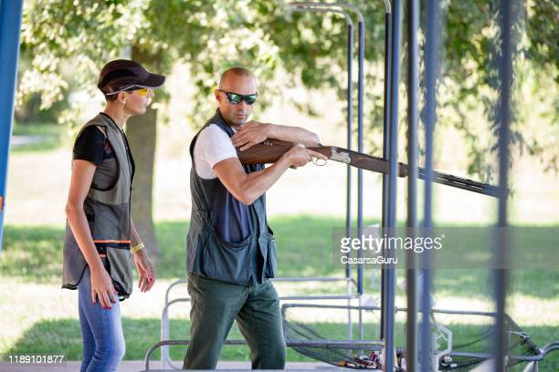 instructor showing adult woman how to lean a shotgun on shoulder before shooting - shotgun stock pictures, royalty-free photos & images
