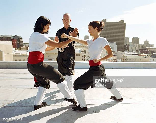 instructor supervising two women practising martial arts on rooftop - combat sport photos et images de collection