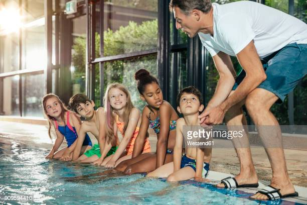 instructor talking to children sitting on poolside in indoor swimming pool - 室内プール ストックフォトと画像