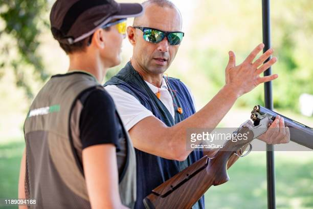 instructor teaching adult woman how to handle a shotgun - shotgun stock pictures, royalty-free photos & images